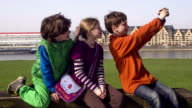 Young Teenagers taking Selfies outdoors, boy orange in front video