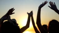 Young teenagers waving their hands in the air at sunset video