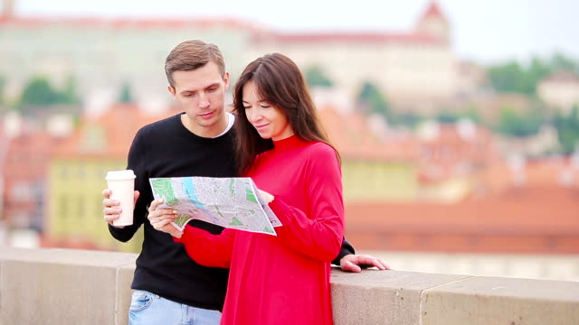 Young tourist couple traveling on holidays in Europe smiling happy. Caucasian family with city map in search of attractions video