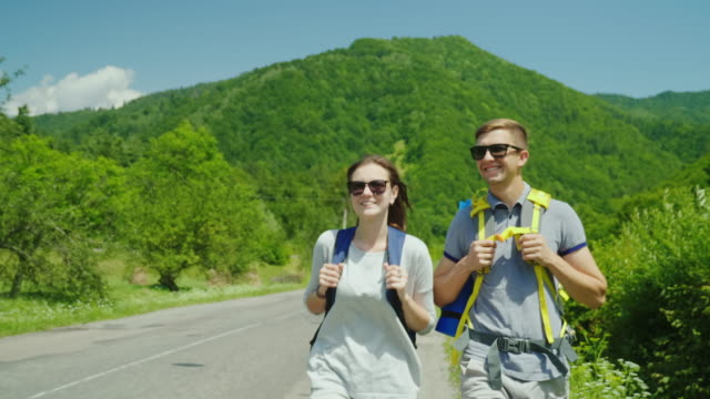 A young tourist couple walks along the road to beautiful mountains covered with forest. Active way of life and vacation video