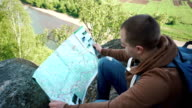 Young tourist man checking his route with map while sitting on shadowed rock boulder with river view downside video
