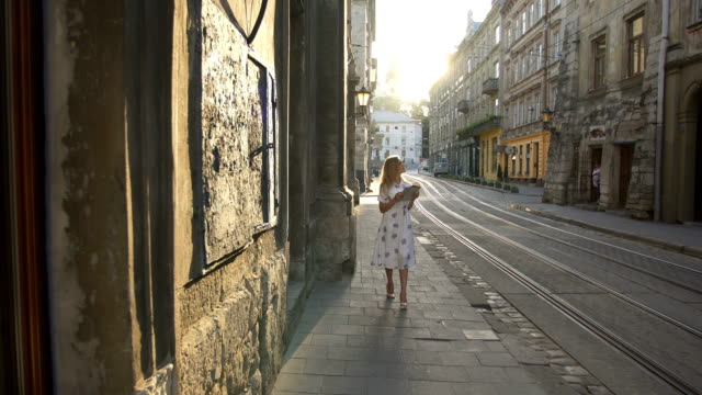 Young tourist woman exploring city map while traveling, vacation concept, flare light video