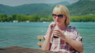 Young tourist woman relaxing in a beautiful location by the lake and mountains in Spain. Drinks Coke from a glass with a straw video