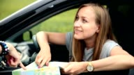 Young tourist woman with car asking for direction video