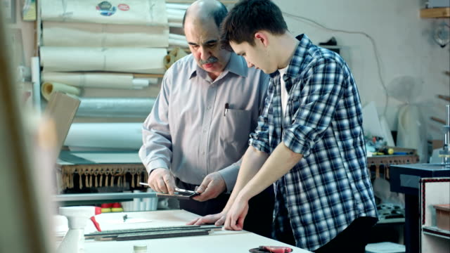 Young trainee studying how to construct a frame, senior worker talking to him behind the desk in frame workshop video