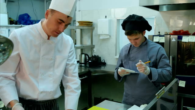 Young trainee watching how chef is cooking and taking notes video