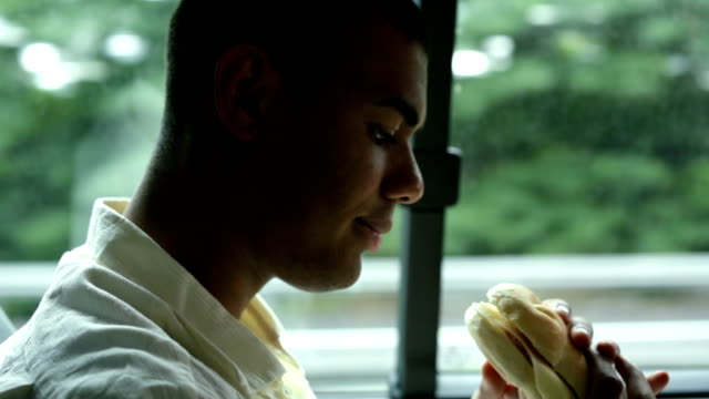 Young traveling man eating sandwich in van video HD video