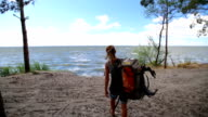 Young Traveller Girl with Curly Hair drops her backpack and comes to the sea video