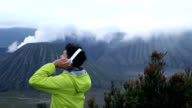 Young traveller listening a music with fresh air on Bromo mount, Indonesia, Asia. Traveling alone Asia. video