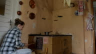 Young villager woman put some firewood in rural kitchen stove. video