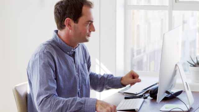 Young white man using phone and computer in an office video
