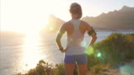 Young woman admiring a coastal view after jogging video