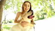 Young woman and her puppy on a swing video