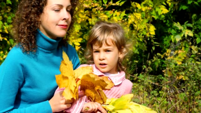 Young woman and little girl with leaves sitting in park video