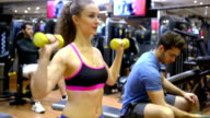 Young woman and man in the gym video