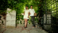 young woman and man standing next to a background of green plants video