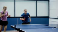 Young woman and man together playing in a table tennis video