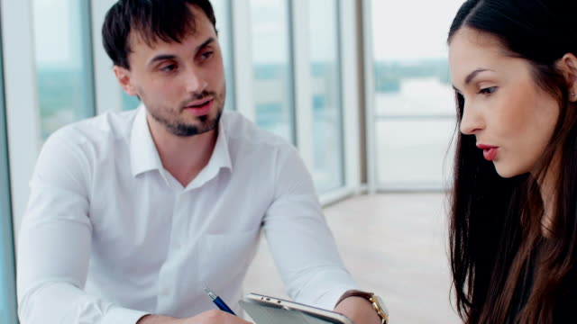 Young woman and man working together, cooperating. video