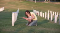 Young woman and son visit grave HD video