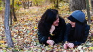 Young woman and teenager laying on leaves video