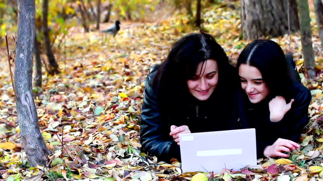 Young woman and teenager laying on leaves with laptop video