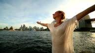 Young woman arms outstretched at Sydney harbour video