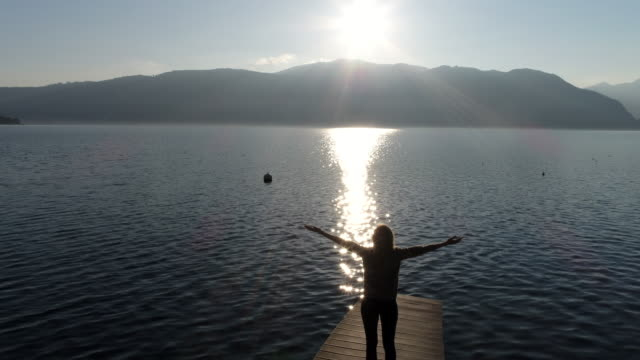 Young woman arms outstretched by the lake video