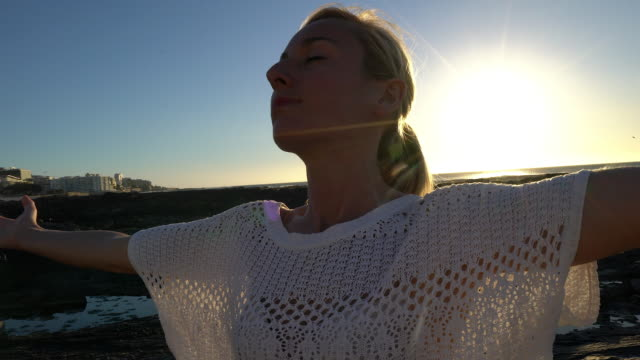 Young woman arms outstretched by the sea at sunset video