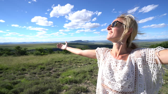 Young woman arms outstretched, mountain landscape video