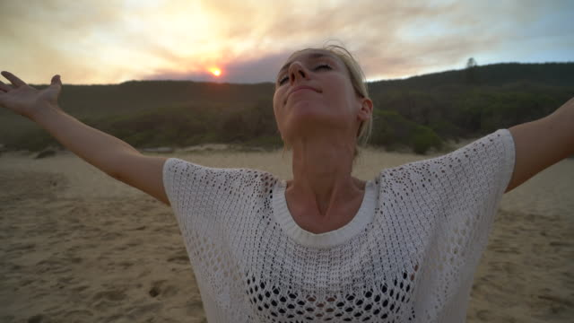 Young woman arms outstretched on beach at sunset video