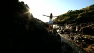 Young woman arms outstretched on steep rock at sunrise video