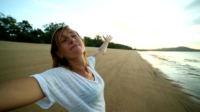 Young woman arms outstretched on the beach at sunrise video
