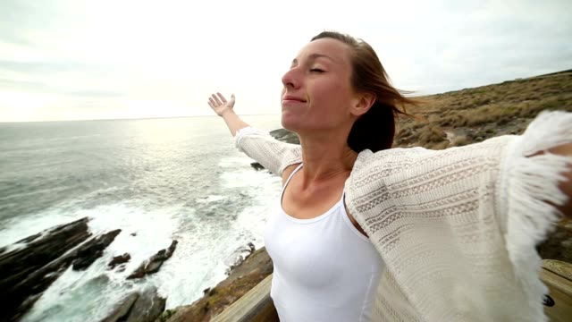 Young woman arms outstretched towards the sea video