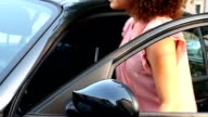 Young woman arrives and seats on her car , and then she's ready to go. The shot gets slowly closer to her face. video