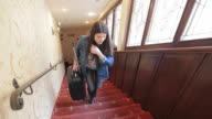 Young woman ascending the stairs in the hotel. video