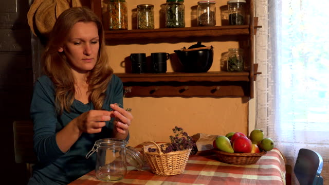 young woman assort herbal thyme glass jar in rural kitchen. FullHD video