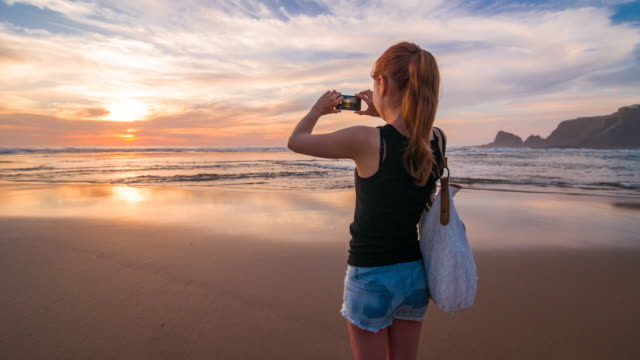 Young woman at beach taking pictures of sunset with phone video