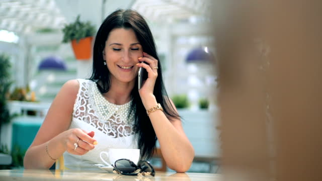 Young woman at cafe drinking coffee and talking on the mobile phone video