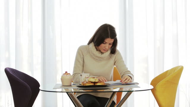 Young woman at home drinking coffee and reading a book. video