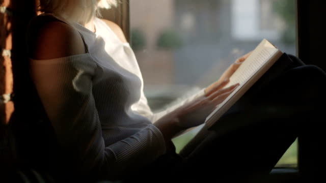 Young woman at home sitting near a window reading book. video