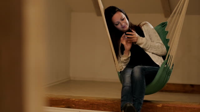 Young woman at home sitting on swing chair video
