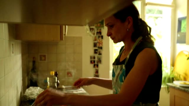 Young woman at the kitchen cooking supper for kid video