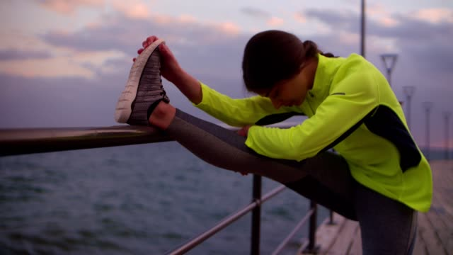 Young woman athlete stretching her legs on a jetty video