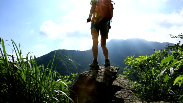 young woman backpacker hiking on mountain peak video