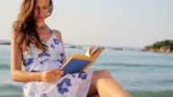 Young Woman Beach Reading Book Sea Vacation Concept HD video