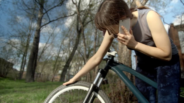 Young woman bicyclist speaks on the phone and tries to fill the tire with air video