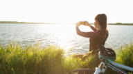 Young woman bicyclist taking picture at the beautiful view. video