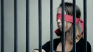 young woman blindfolded behind prison bars video