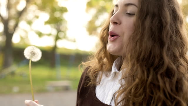 Young woman blowing a dandelion video