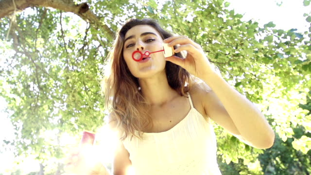 Young woman blowing bubbles in park in slow motion video